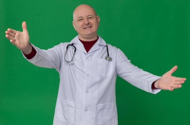 Blij volwassen slavische man in doktersuniform met stethoscoop die handen open houdt