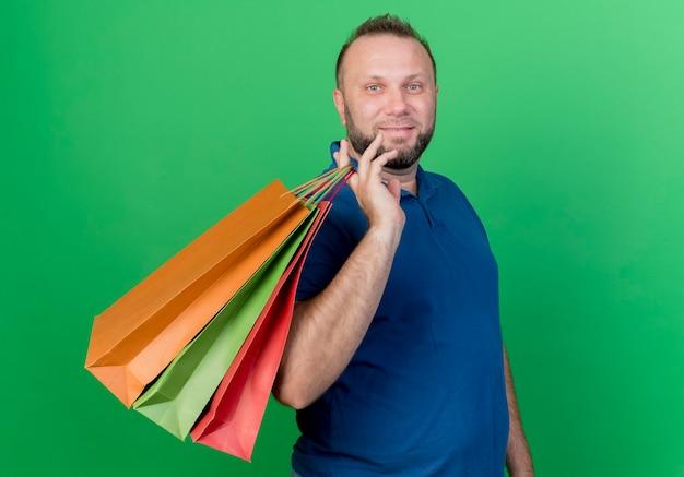 Blij volwassen slavische man met boodschappentassen op schouder geïsoleerd op groene muur met kopie ruimte