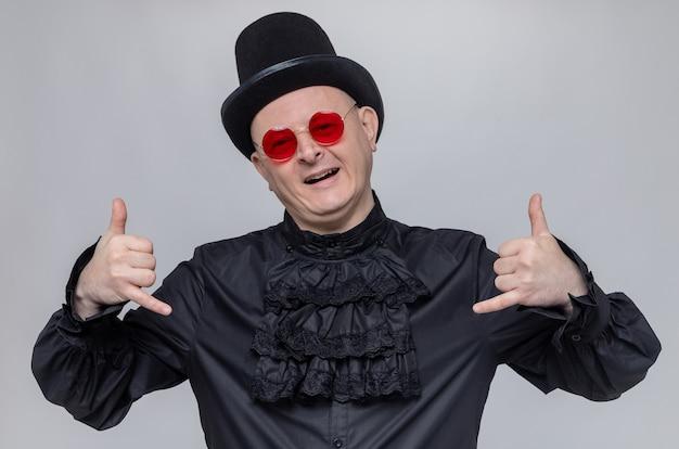 Blij volwassen slavische man met hoge hoed en met zonnebril in zwart gothic shirt gebaren hangen los teken