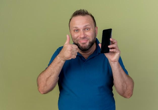Blij volwassen slavische man op zoek met mobiele telefoon en duim opdagen