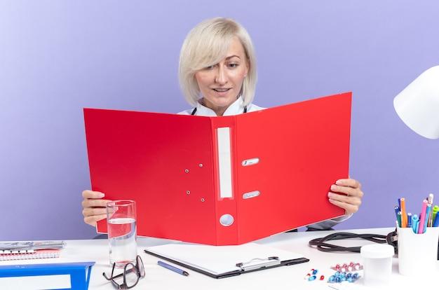 Blij volwassen slavische vrouwelijke arts in medisch gewaad met stethoscoop zittend aan een bureau met office tools houden en kijken naar bestandsmap geïsoleerd op paarse muur met kopie ruimte