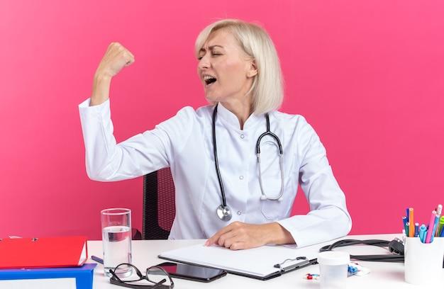 Blij volwassen vrouwelijke arts in medische gewaad met stethoscoop zit aan bureau met office tools spannen biceps geïsoleerd op roze muur met kopie ruimte