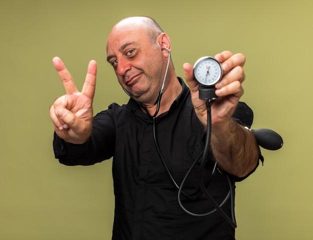 Blij volwassen zieke blanke man met bloeddrukmeter en gebaren overwinning teken geïsoleerd op olijf groene muur met kopie ruimte