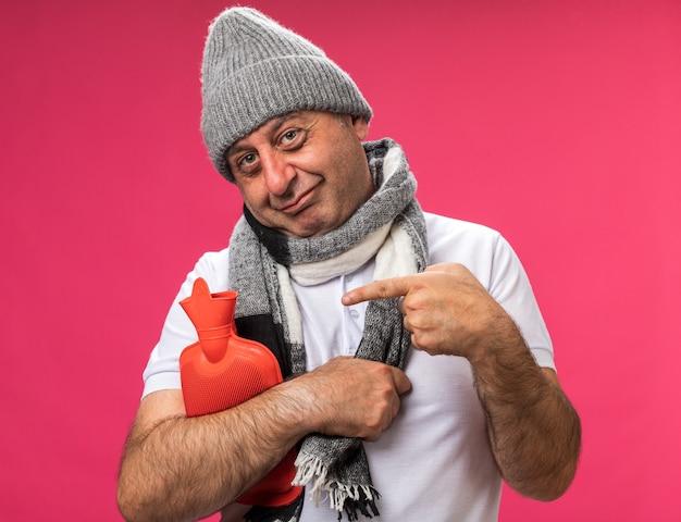 Blij volwassen zieke blanke man met sjaal om de nek met een wintermuts die vasthoudt en wijst naar een warmwaterkruik geïsoleerd op een roze muur met kopieerruimte