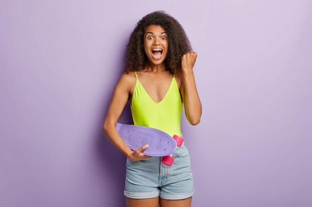 Blij vreugdevolle sportieve vrouw poseren met skateboard