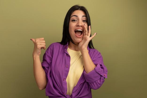 Blij vrij donkerbruin kaukasisch meisje houdt hand dicht bij mond en wijst terug op olijfgroen