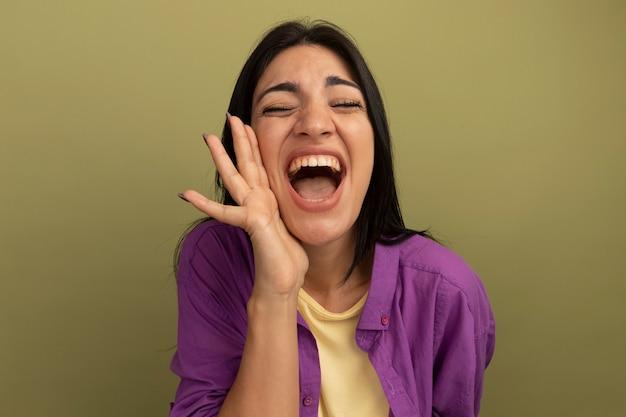 Blij vrij donkerbruin kaukasisch meisje houdt hand dicht bij mond op olijfgroen