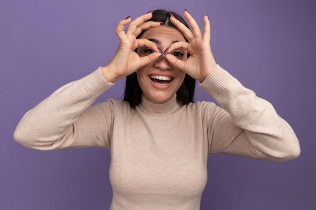 Blij vrij donkerbruin kaukasisch meisje in zonnebril bekijkt camera door vingers op paars