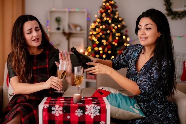 Blij vrij jong meisje gebaren genoeg met de hand naar vriend champagne gieten in haar glas zittend op een fauteuil en genieten van kersttijd thuis