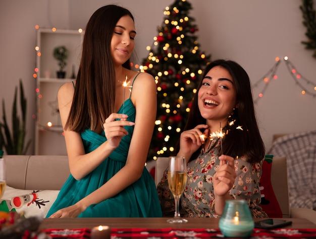 Blij vrij jong meisje houdt wonderkaarsen en kijkt naar haar vriend zittend aan tafel en genieten van kersttijd thuis