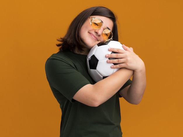 Blij, vrij kaukasisch meisje in zonnebril knuffelt bal geïsoleerd op oranje muur met kopieerruimte