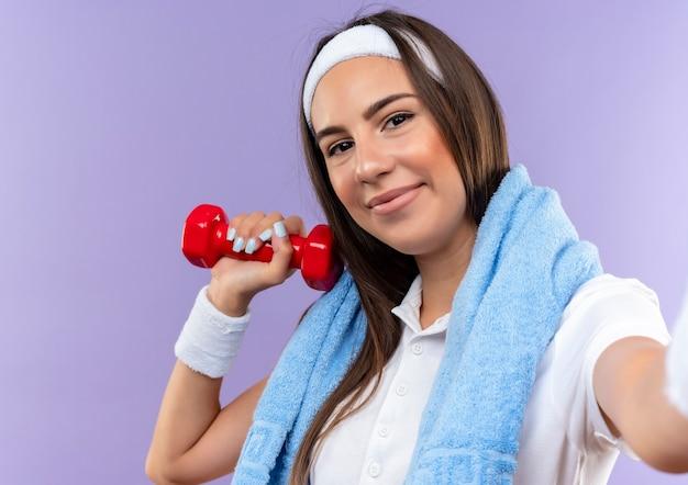 Blij vrij sportief meisje die hoofdband en polsbandje dragen die halter met handdoek om hals houden die op purpere ruimte wordt geïsoleerd