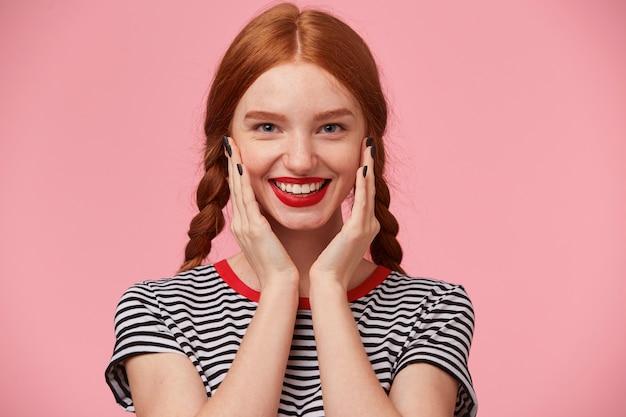 Blij, vrolijk mooi roodharig meisje met twee vlechten houdt handen in de buurt van haar gezicht en lacht gelukkig met rode lippen, witte gezonde tanden tonen, geïsoleerd