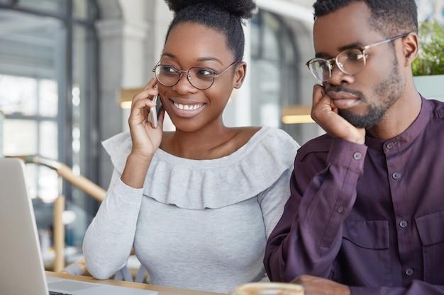Blij vrolijk vrouwtje met donkere huid spreekt met vriend via de mobiele telefoon, zit voor geopende laptopcomputer met afrikaanse man