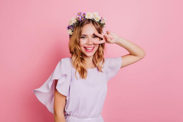 Blij vrouw in schattige krans poseren op lichte muur met vredesteken
