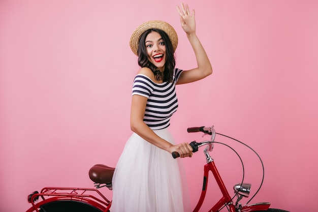 Blij vrouw in strohoed poseren op fiets met verbaasde glimlach. binnen schot van aantrekkelijk donkerbruin meisje dat gelukkige emoties uitdrukt.