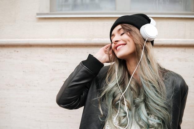 Blij vrouw in warme kleren luisteren muziek op straat