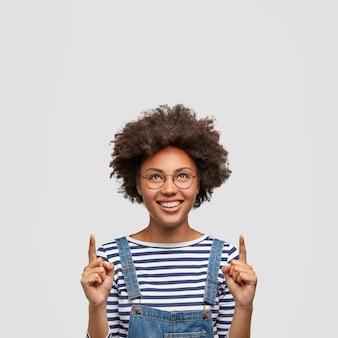 Blij vrouw met brede glimlach, wijst naar boven, gekleed in modieuze kleding