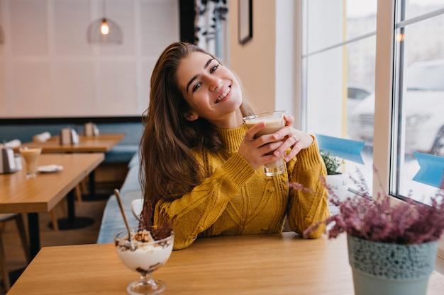 Blij vrouw met donker haar koelen met kopje koffie in gezellig café in de winter. indoor portret van geweldige dame in gebreide gele cardigan rusten in restaurant en genieten van ijs.