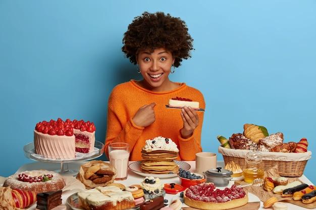 Blij vrouw met donkere huid heeft een positieve blik, wijst naar zichzelf, houdt lekker stuk taart vast, vraagt of ze alles moet opeten, gekleed in een oranje trui, geïsoleerd op een blauwe muur.