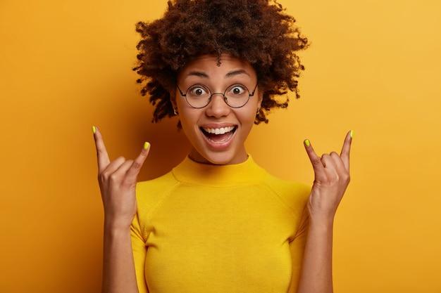 Blij vrouw met donkere huidskleur maakt heavy metal-rockbord, lacht positief, luistert naar favoriete muziekgenre, draagt casual geel t-shirt, poseert binnen. rock n roll om ons heen. lichaamstaal concept
