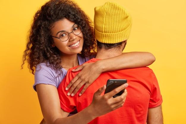 Blij vrouw met donkere huidskleur met afro-kapsel, draagt een ronde bril, omhelst de man in een gele hoed en een rood t-shirt, houdt een mobiele telefoon vast, wacht op een belangrijk telefoontje. mensen, technologie, relatieconcept