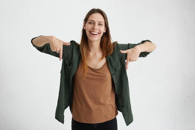 Blij vrouw met ovaal gezicht, donker steil haar in een groene jas en een bruin shirt dat met haar wijsvingers naar beneden wijst en een vrolijke blik heeft