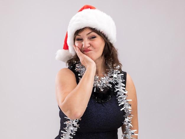 Blij vrouw van middelbare leeftijd dragen kerstmuts en klatergoud slinger rond nek kijken camera houden hand op gezicht geïsoleerd op een witte achtergrond met kopie ruimte