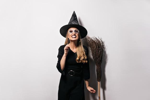 Blij vrouwelijk model in het grappige halloween-kostuum stellen. emotioneel blondemeisje in heksenhoed die zich op witte muur bevinden.