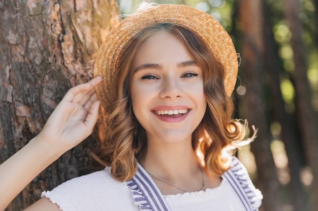 Blij vrouwelijk model in hoed glimlachend in de zomerdag. buiten schot van verfijnd krullend meisje lachen op bos.