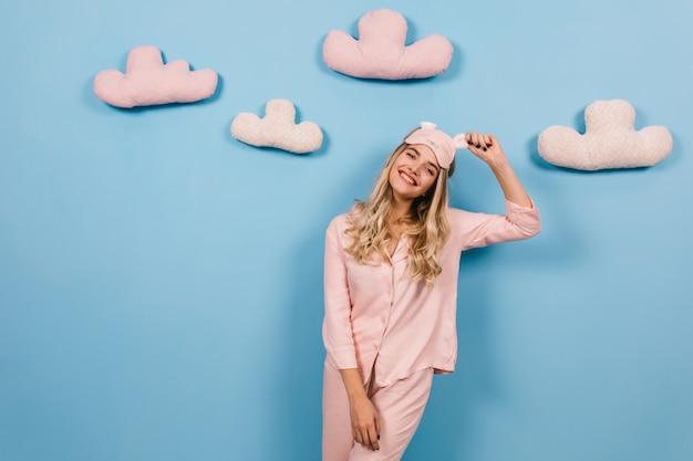 Blij vrouwelijk model in roze pyjama dat geluk uitdrukt