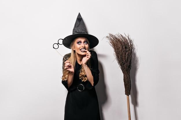 Blij vrouwelijk model met donkere make-up die op carnaval voorbereidingen treffen. jocund meisje in halloween kostuum grappige gezichten maken.