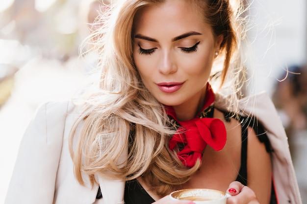 Blij vrouwelijk model met trendy make-up naar beneden te kijken terwijl je een kopje cappuccino vasthoudt. close-upportret van europees blondemeisje die van koffiesmaak genieten met gesloten ogen.