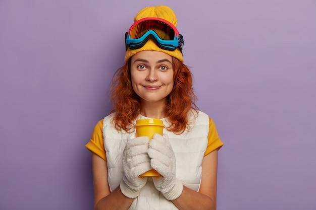Blij vrouwelijke skiër heeft koffiepauze, draagt witte wanten, t-shirt, gele hoed en beschermende snowboardbril, glimlacht met kuiltjes, geïsoleerd op paarse achtergrond.