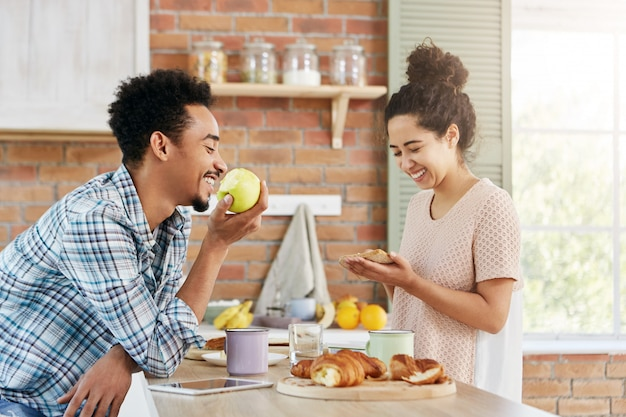 Blij vrouwtje maakt sandwich, praat met echtgenoot die tegenover haar zit, eet appel. familiepaar brengt samen vrije tijd door,