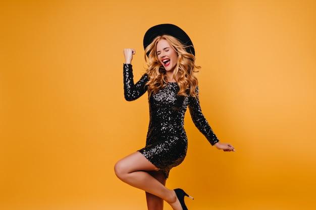 Blij welgevormd meisje dat in hoed op gele muur springt. aantrekkelijke langharige dame in zwarte jurk dansen op feestje.
