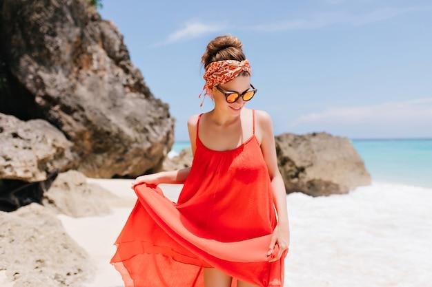 Blij wit vrouwelijk model in zonnebril die bij strand met rotsen koelen. leuk kaukasisch meisje speelt met haar rode jurk in de buurt van de oceaan.