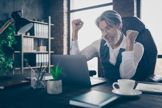 Blij zakenman kijken in laptop vieren overwinning vuisten opheffen in kantoor
