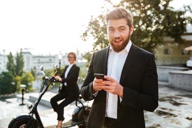 Blij zakenman poseren buitenshuis met behulp van de telefoon