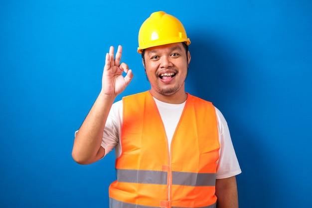 Blij zelfverzekerde dikke aziatische constructuin werknemer man met brede glimlach