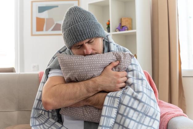 Blij zieke slavische man met sjaal om nek dragen wintermuts gewikkeld in plaid houden en hoofd op kussen zittend op de bank in de woonkamer