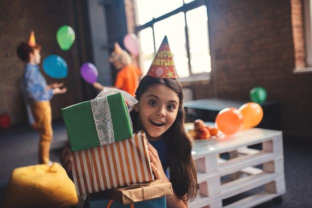 Blij zijn. leuk meisje in een hoed met cadeautjes en gelukkig gevoel