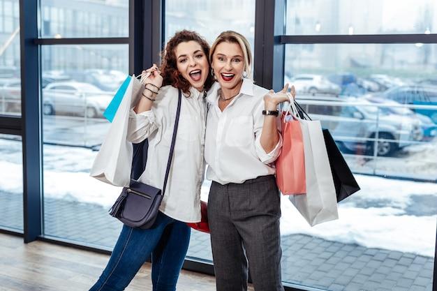 Blij zijn. stijlvolle knappe moeder en dochter voelen zich gelukkig bij het verlaten van het winkelcentrum