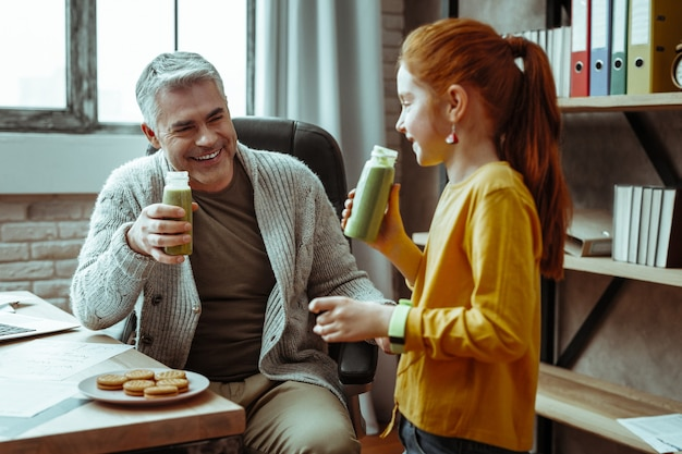Blij zijn. vrolijke positieve man die lacht naar zijn dochter terwijl hij sap drinkt met haar