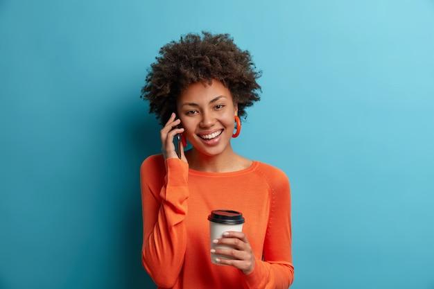 Blij zorgeloos etnisch duizendjarig meisje heeft een aangenaam telefoongesprek, houdt de slimme telefoon bij het oor, heeft een schattige glimlach en een gelukkig humeur, drinkt een aromatische drank, draagt een oranje trui, geïsoleerd op blauw