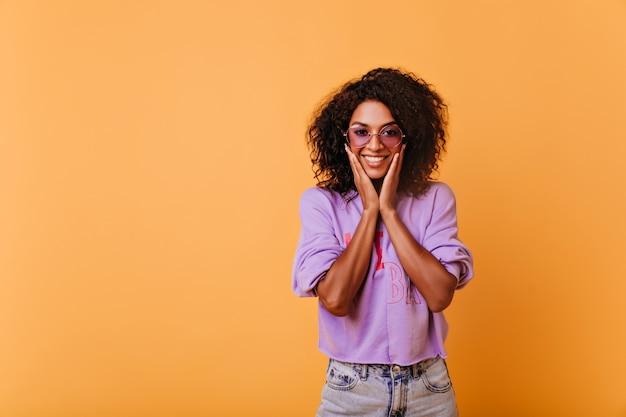Blij zwart meisje in trendy zonnebril met plezier tijdens indoor shotshoot. verfijnde stijlvolle afrikaanse vrouw lachend speels op geel.