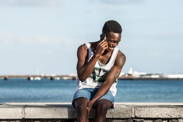 Blij zwarte man praten op smartphone op dijk