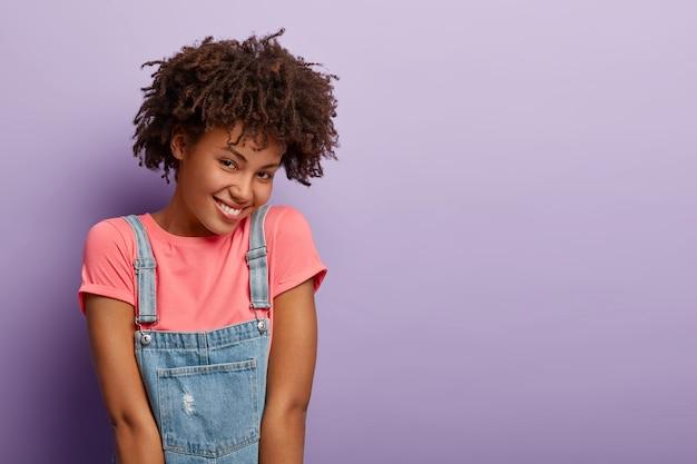 Blije afro-amerikaanse vrouw heeft een vrolijke verlegen gezichtsuitdrukking, drukt positieve emoties uit, draagt een roze t-shirt en denim sarafan, modellen over paarse muur, kopie ruimte opzij