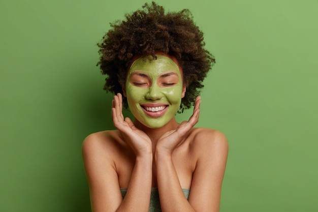 Blije afro-amerikaanse vrouw raakt gezicht zachtjes aanbrengt groen voedend masker glimlacht zachtjes staat blote schouders binnen voelt verfrist na het douchen