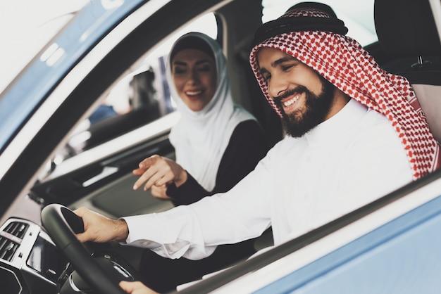Blije arabische zakenman glimlacht naar nieuwe auto.